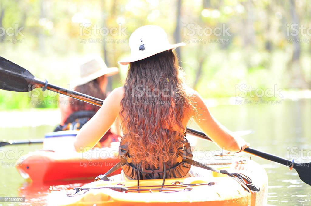 Washed-out rear view of two teenage girls kayaking stock photo