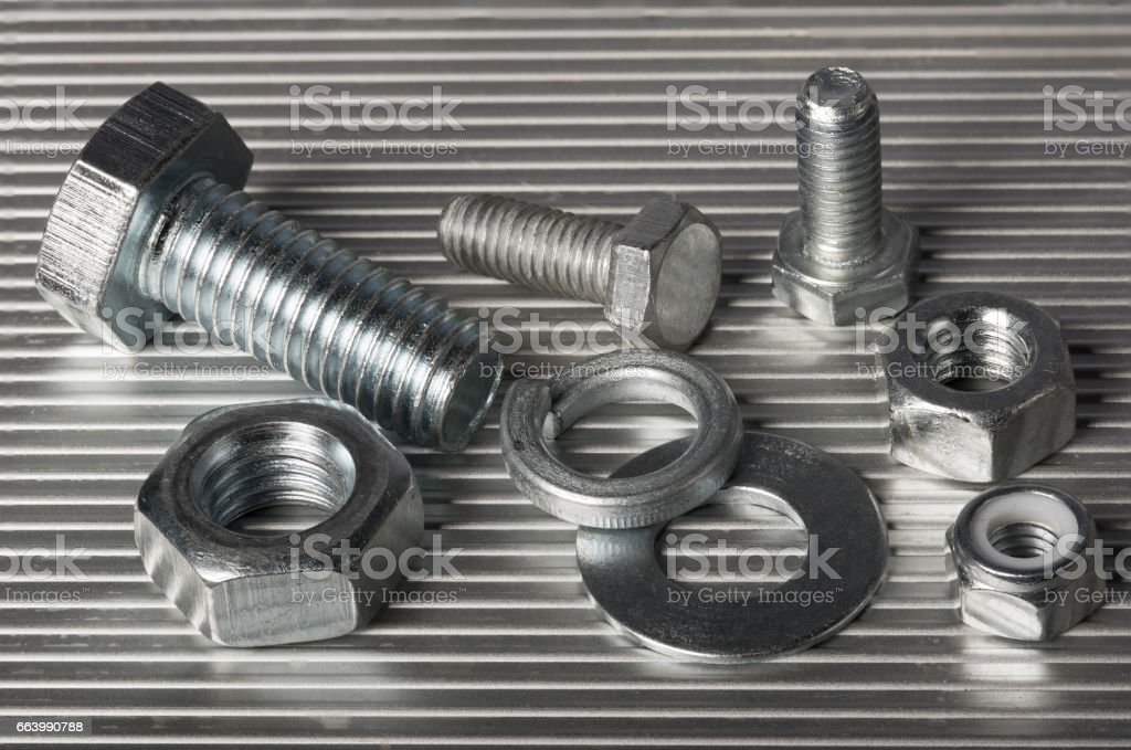 Washers,  bolts and nuts on the aluminum background. stock photo