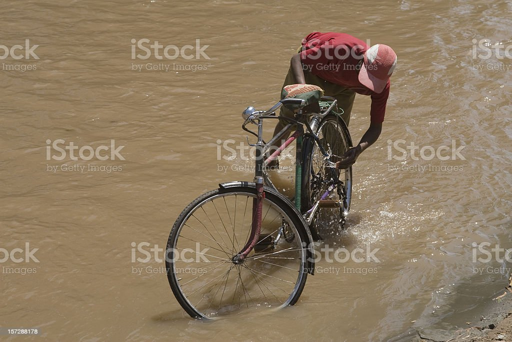 Washing a bicycle in the river stock photo