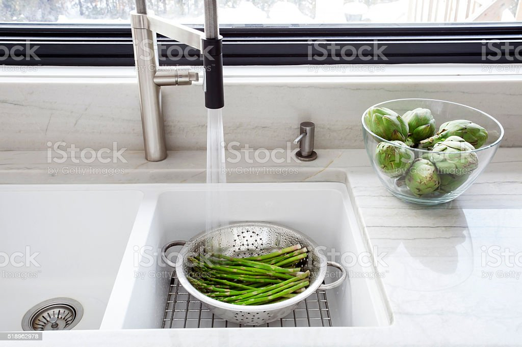 Washing fresh asparagus in the Kitchen sink. stock photo
