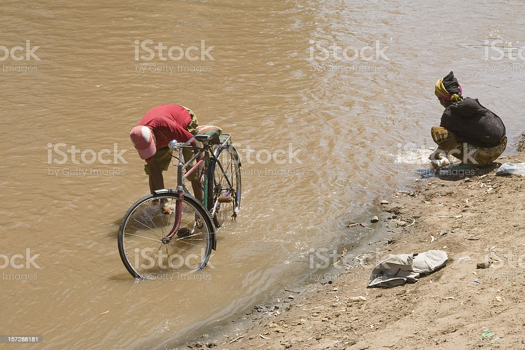 Washing laundry and a bicycle in the river stock photo