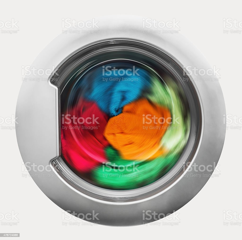 Washing machine door with rotating garments inside stock photo
