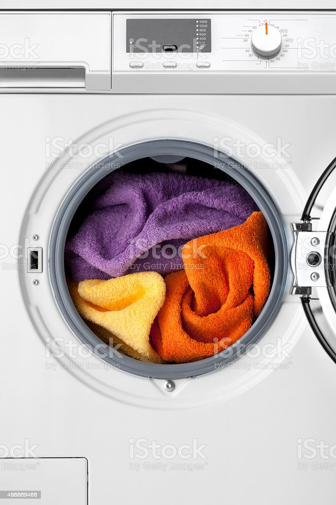 Washing machine with colorful clothes inside stock photo