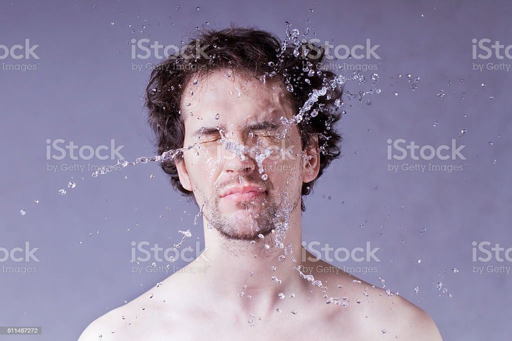 Washing up. Handsome man with splashing water on his face. stock photo