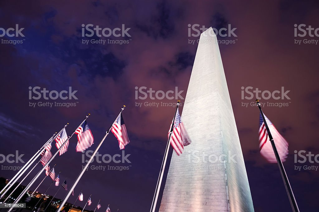 Washington Monument with American flags along National Mall at night stock photo