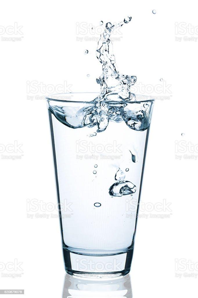 Wasserglas mit spritzendem Wasser und Tropfen stock photo