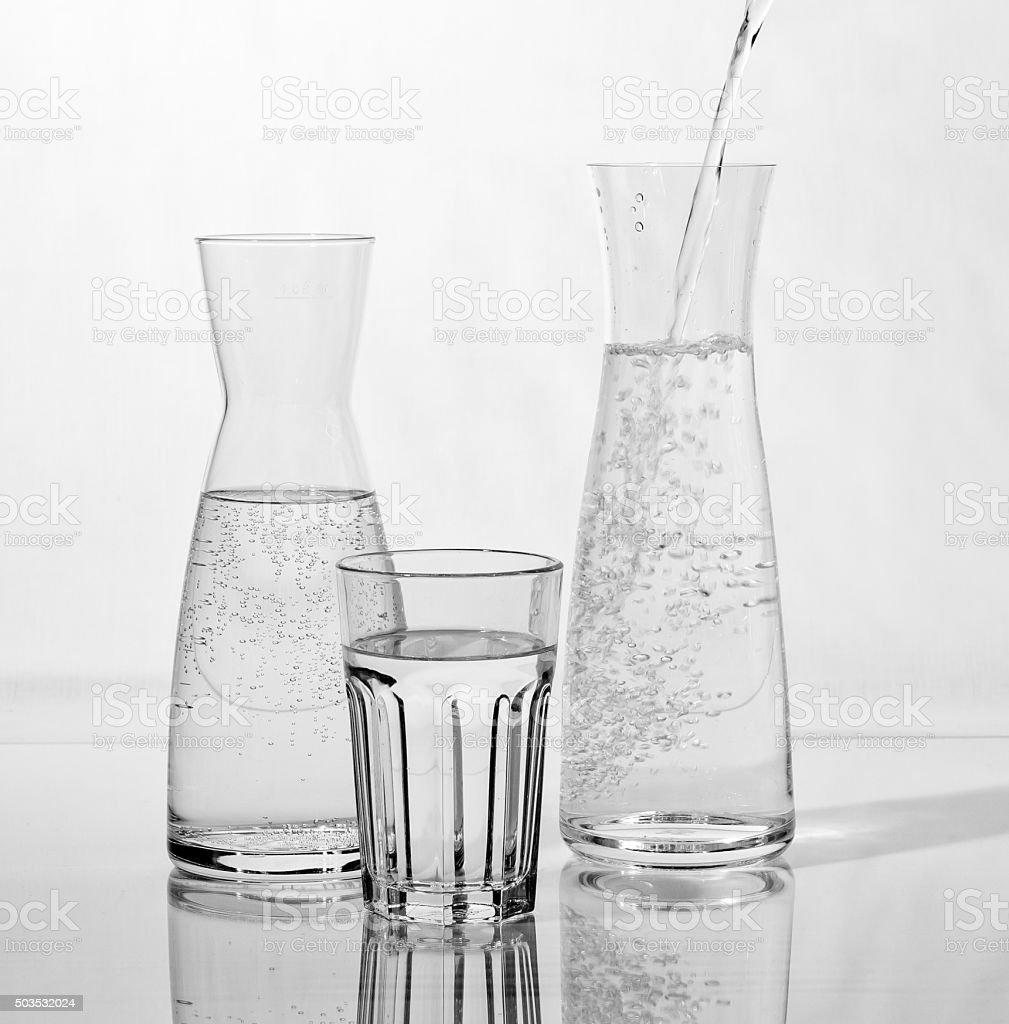 Wasserkaraffe wird mit Trinkwasser gefüllt stock photo