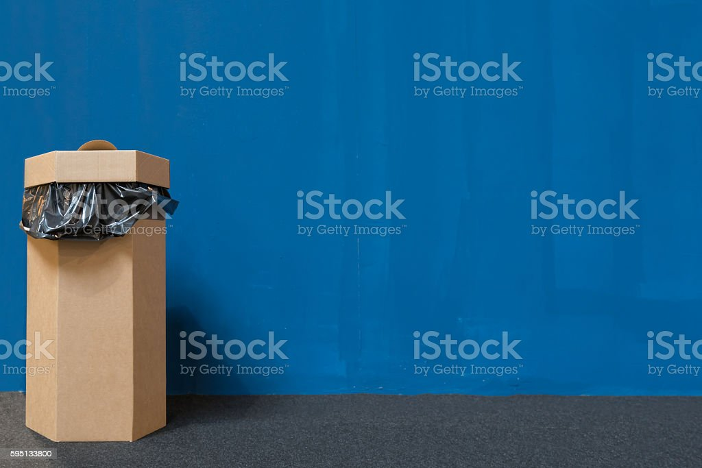 Waste bin made of recycled paper, blue painted wall background stock photo