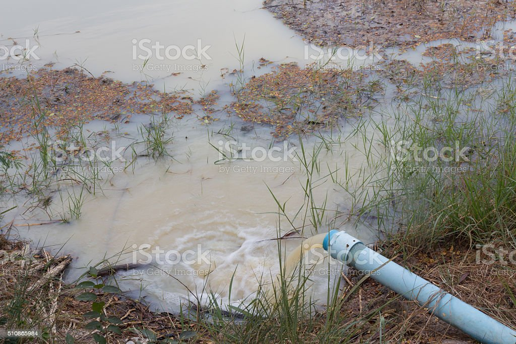 Waste water running from a pipeline to pond stock photo