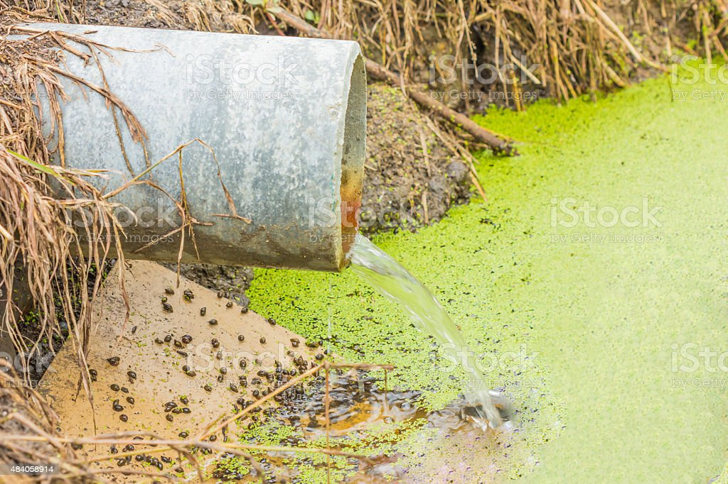 waste water running slow from a concrete pipeline stock photo