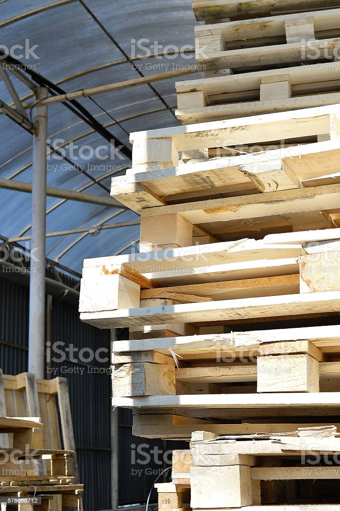 Waste wood from pallets stacked in the storage room stock photo