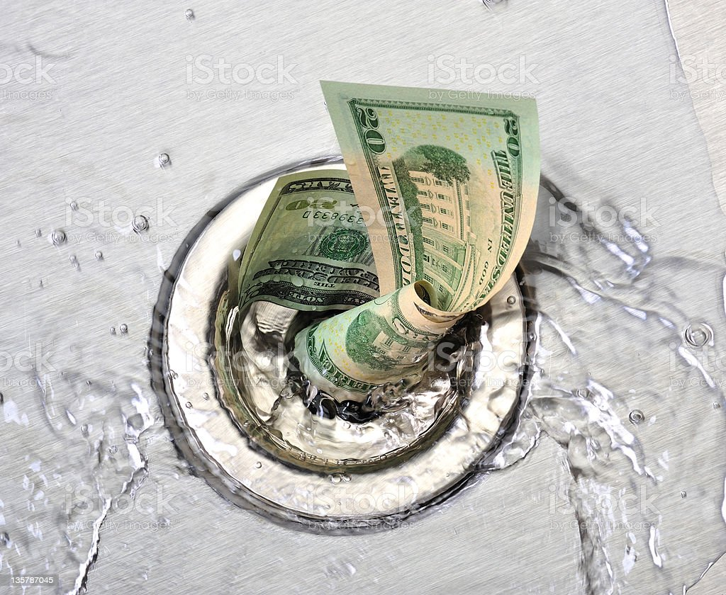 Wasted money going down the sink drain stock photo