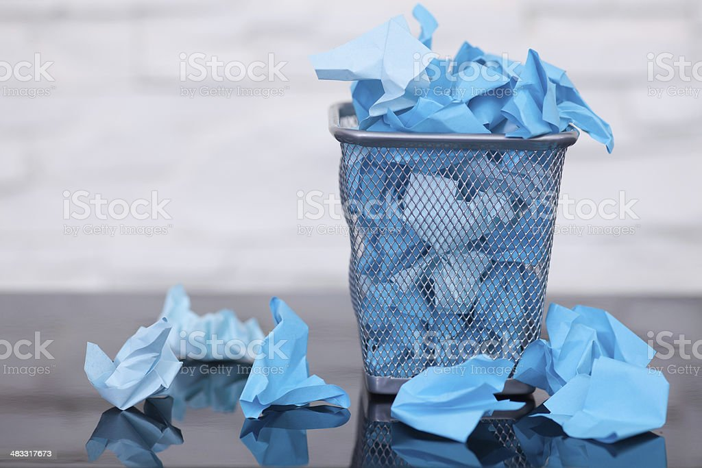 Wastepaper basket with wrinkled paper stock photo