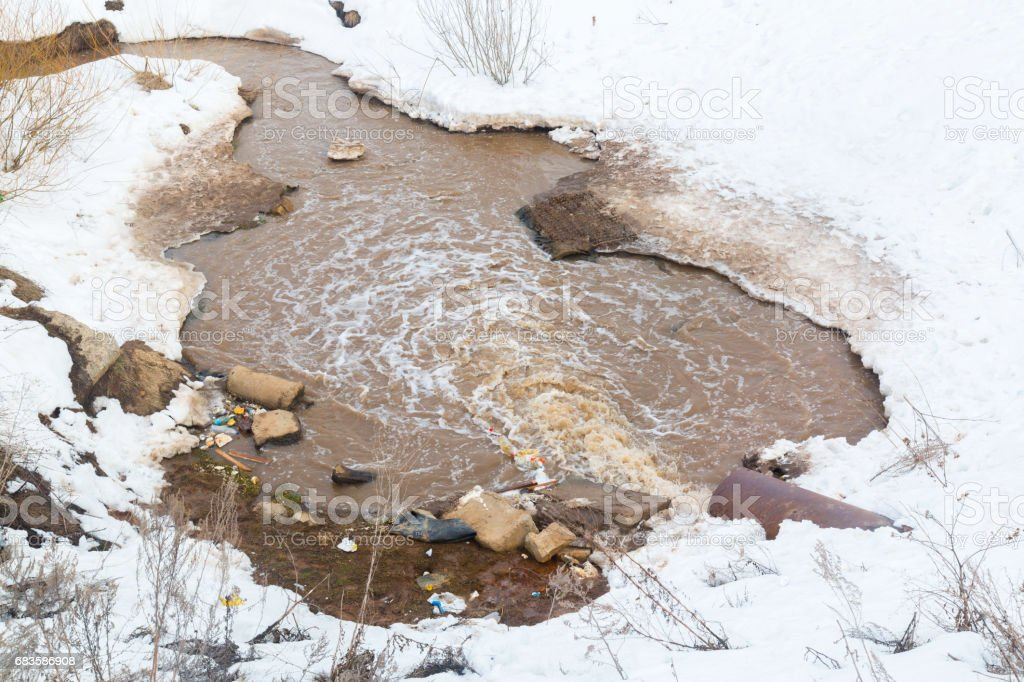 Wastewater pollutes the environment. Dirty puddle. stock photo