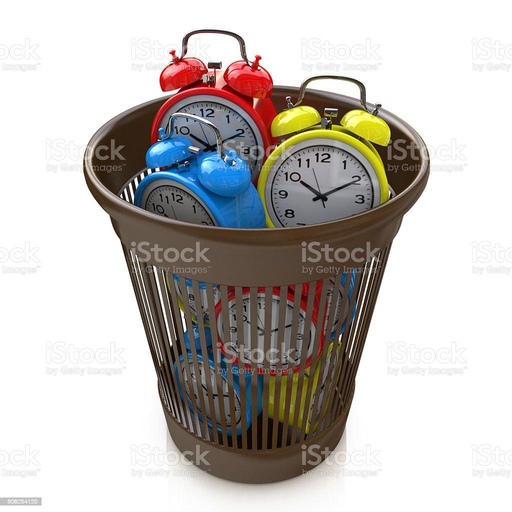 Wasting time concept: alarm clocks in the trash bin stock photo