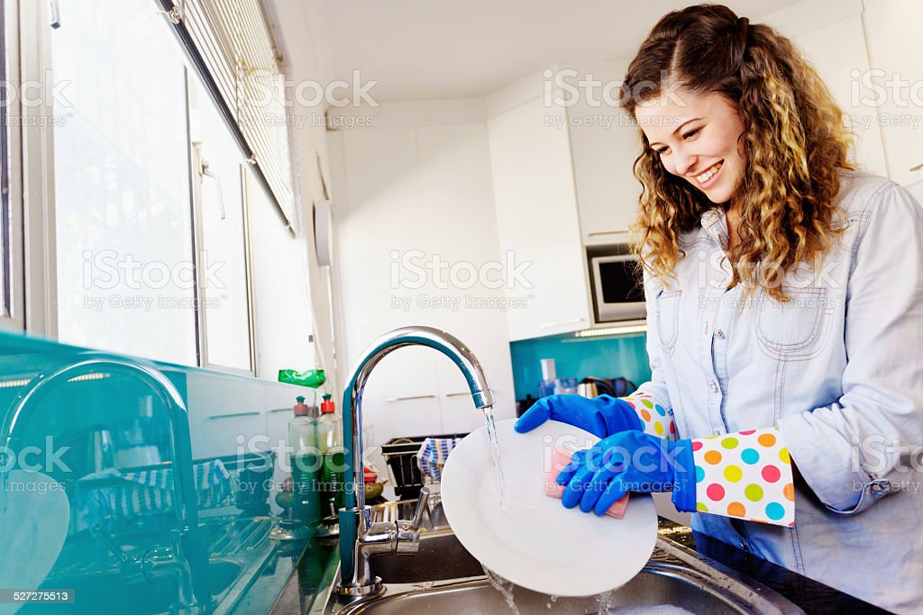 Wasting water! Young beauty does the dishes under running faucet stock photo