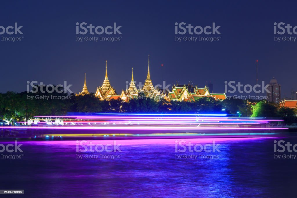 wat phra kaew with blur light of boat moving passed stock photo