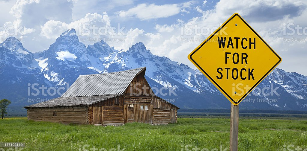 Watch for stock sign with Tetons and barn stock photo