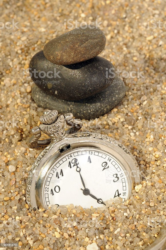 watch in the sand and pebble balance. time concept stock photo