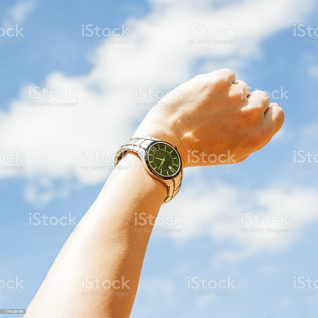 Watch on arm with blue sky stock photo