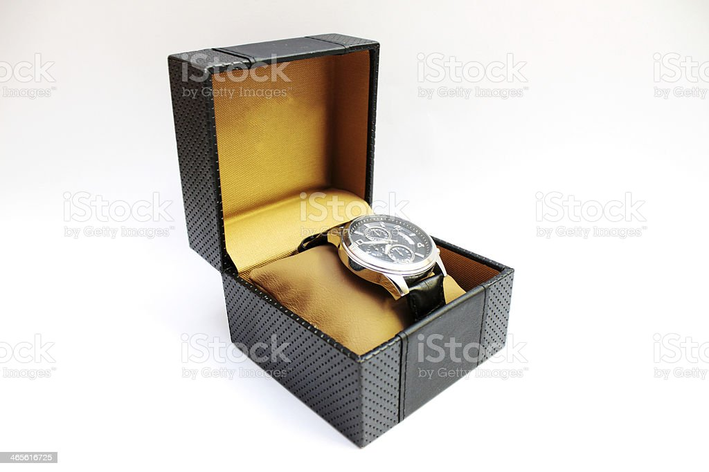Watch on yellow pillow in back gift box on white background stock photo