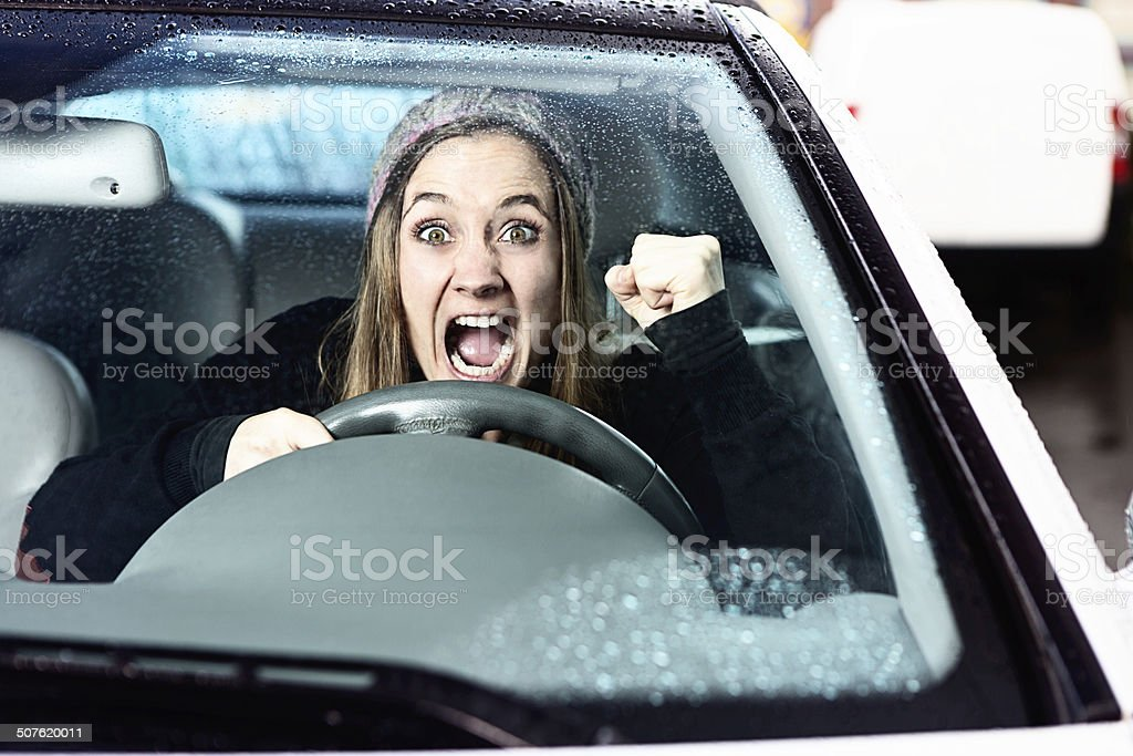 Watch out! Enraged woman driver shakes her fist stock photo