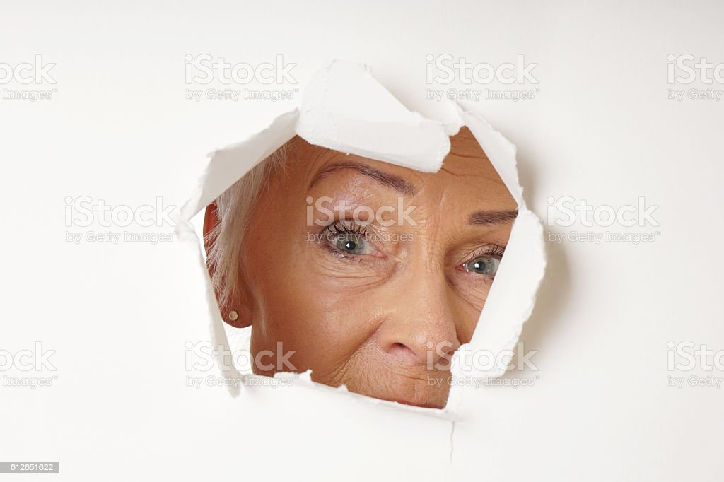 watchful older woman looking through hole stock photo