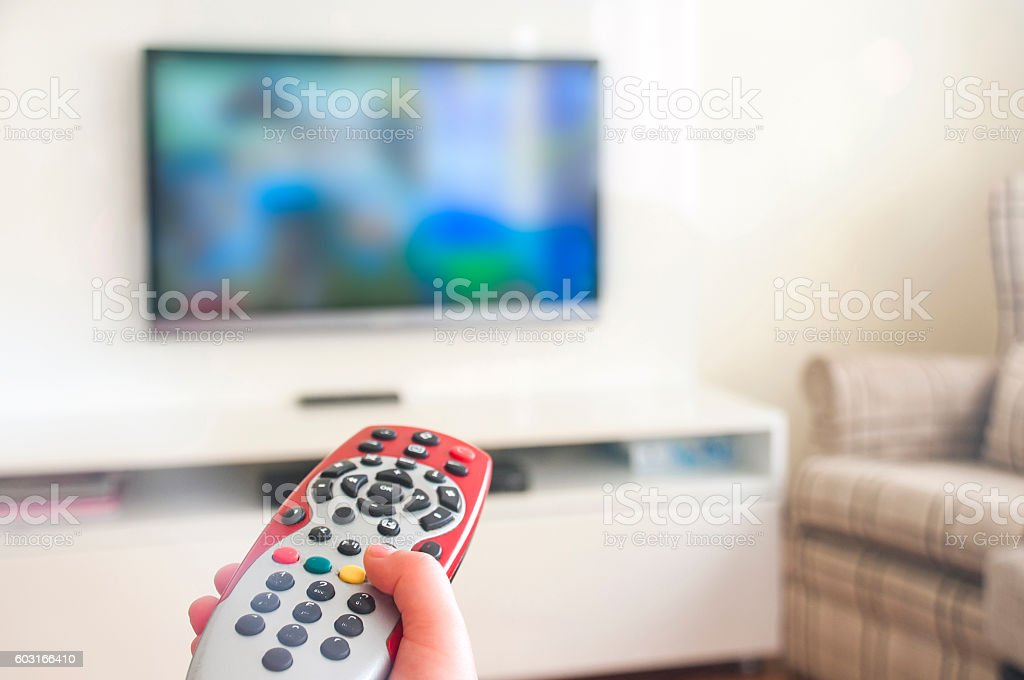 Watching animated cartoon on TV remote control in hand stock photo