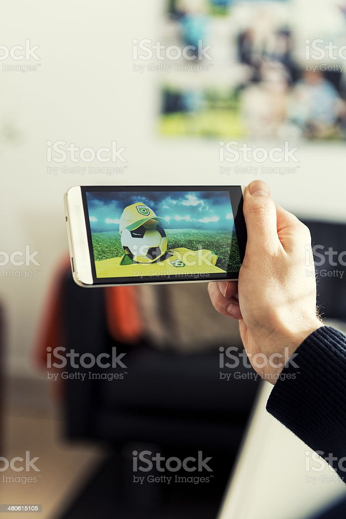 Watching Brazil soccer on a mobile phone royalty-free stock photo