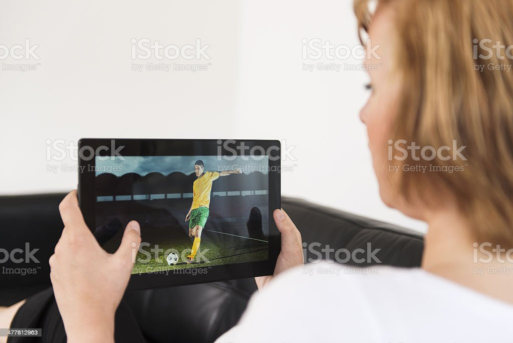 Watching football game on a digital tablet royalty-free stock photo