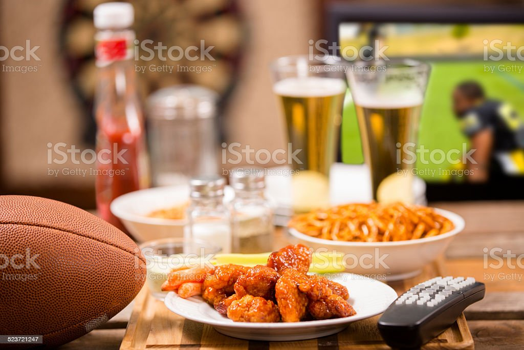 Watching football game on television at local pub. Food, beer. stock photo