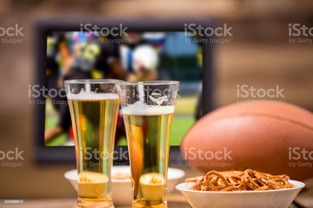 Watching football game on television. Snacks, beer, ball. stock photo