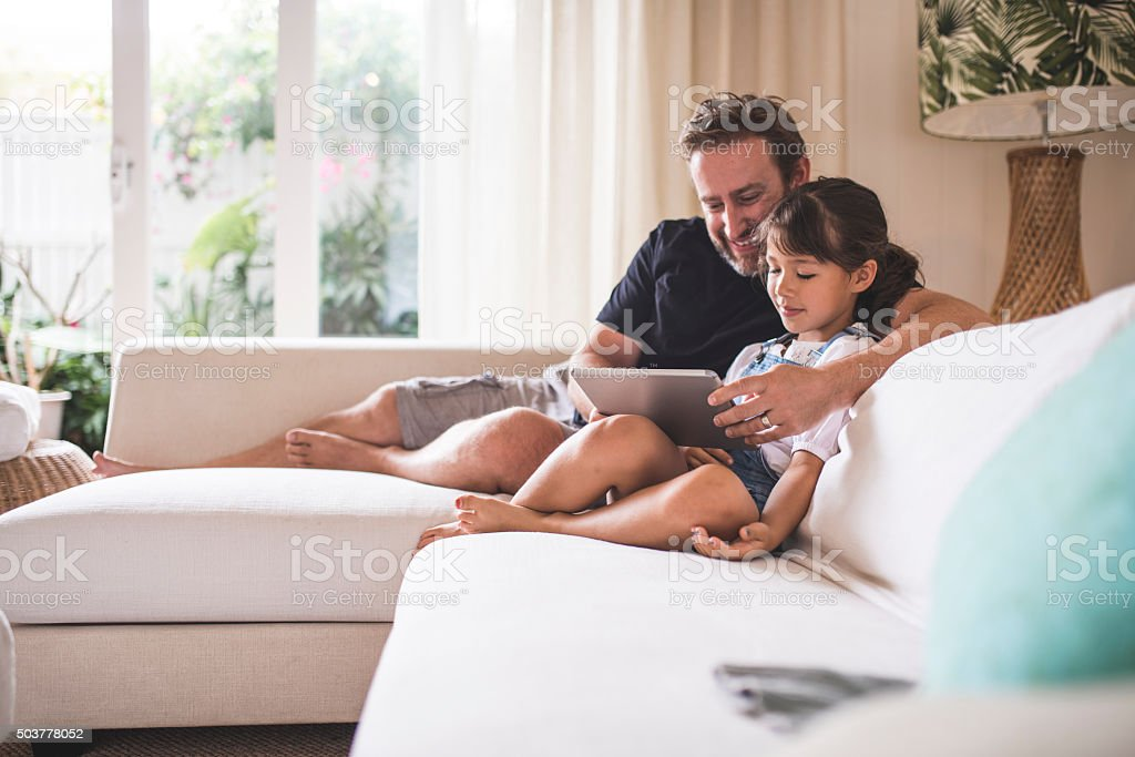 Watching funny videos with her dad stock photo