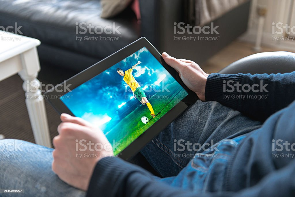 Watching live streaming of a soccer match on digital tablet stock photo