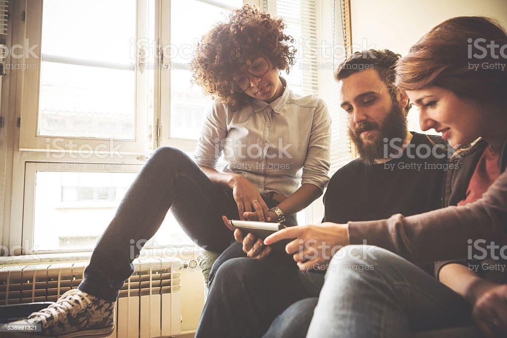 Watching pictures on the smartphone together stock photo