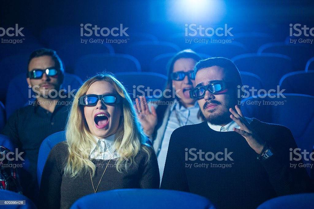 Watching scary movie at the cinema stock photo