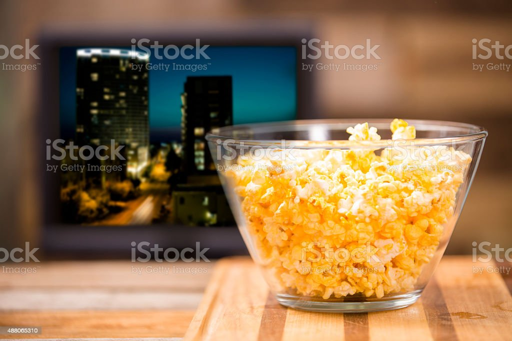 Watching show, movie on television at home. Popcorn. stock photo