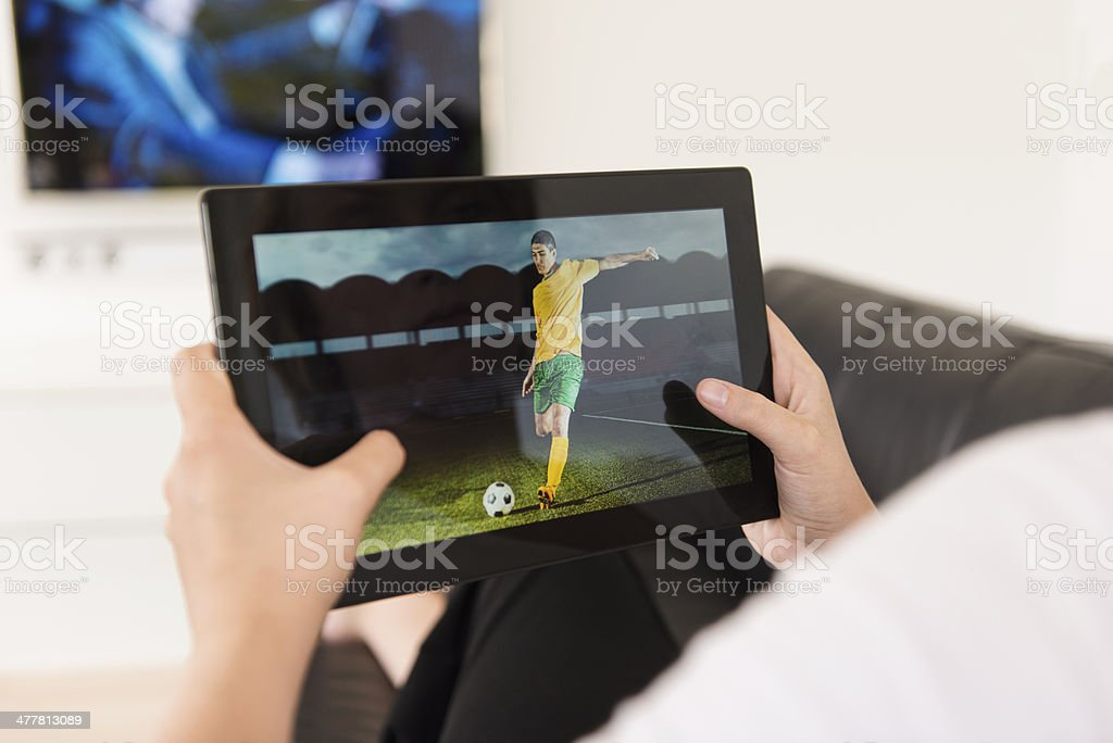 Watching soccer game on a digital tablet royalty-free stock photo