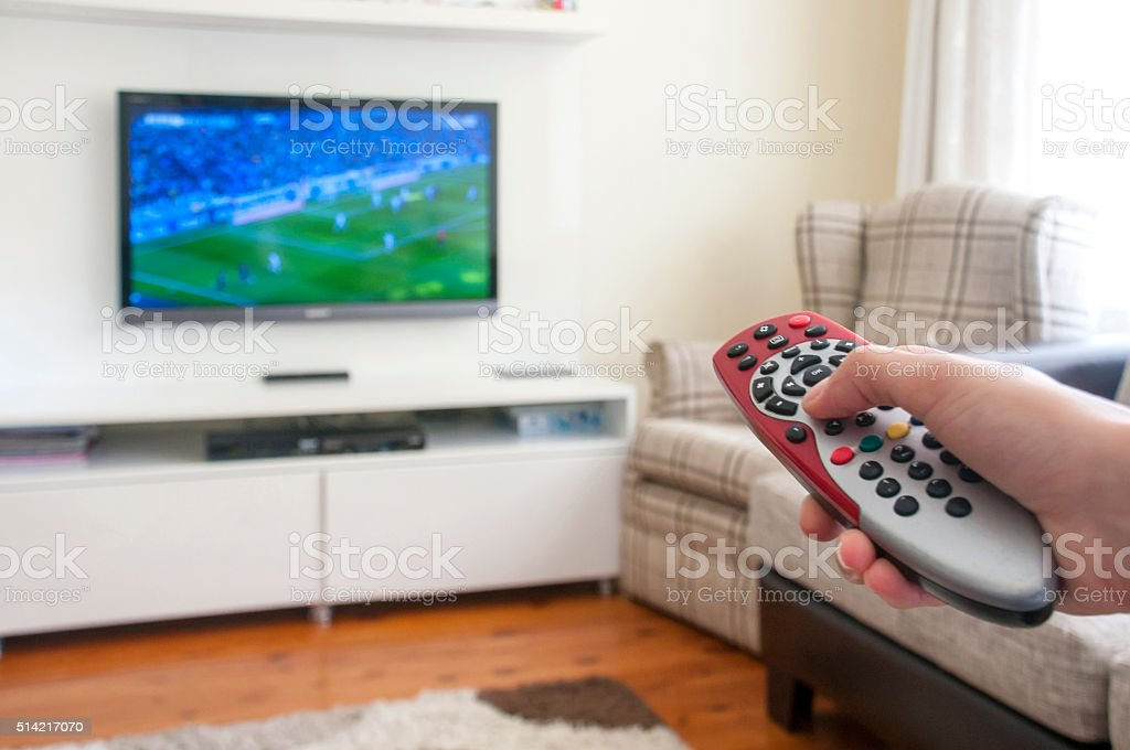 Watching soccer on a smart TV remote control in hand stock photo
