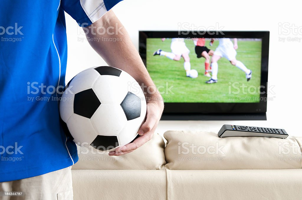 Watching soccer on tv with football jersey and ball royalty-free stock photo