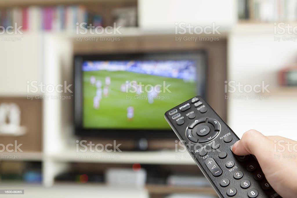 watching soccer with TV remote control in hand royalty-free stock photo