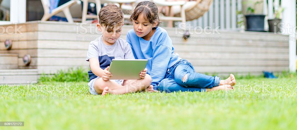 Watching something on a digital tablet on grass stock photo