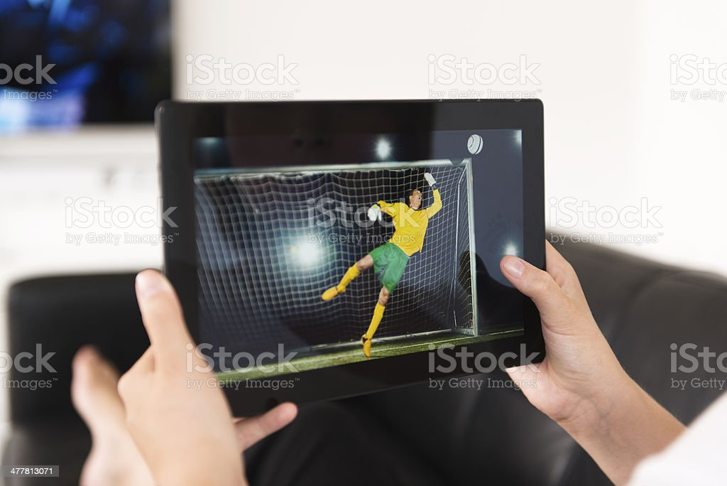 Watching sport event on a digital tablet royalty-free stock photo