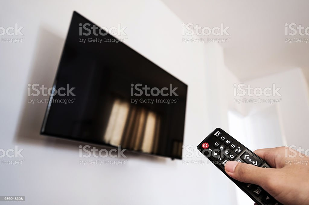 Watching Television, Hand using remote TV stock photo