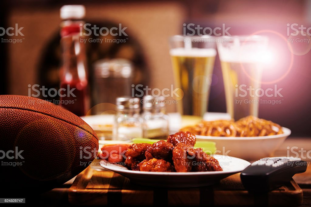 Watching television. Sports bar or local pub. Football, food, beer. stock photo