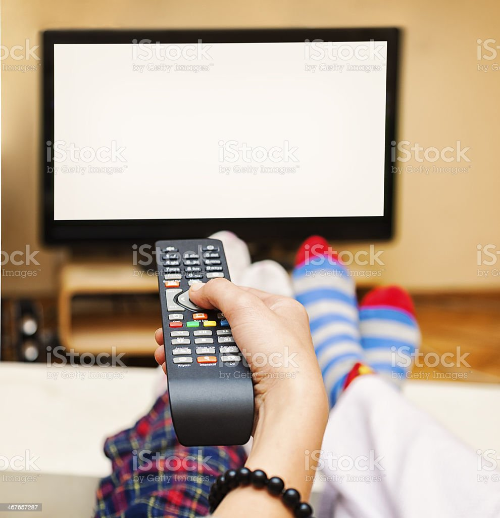 Close-up of a Hand Holding a Remote Control, TV showing white blank...