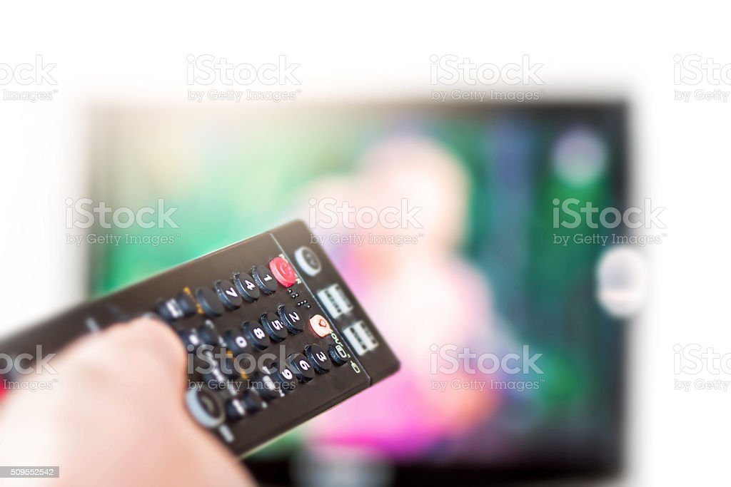 Watching TV selective focus on remote control in foreground stock photo