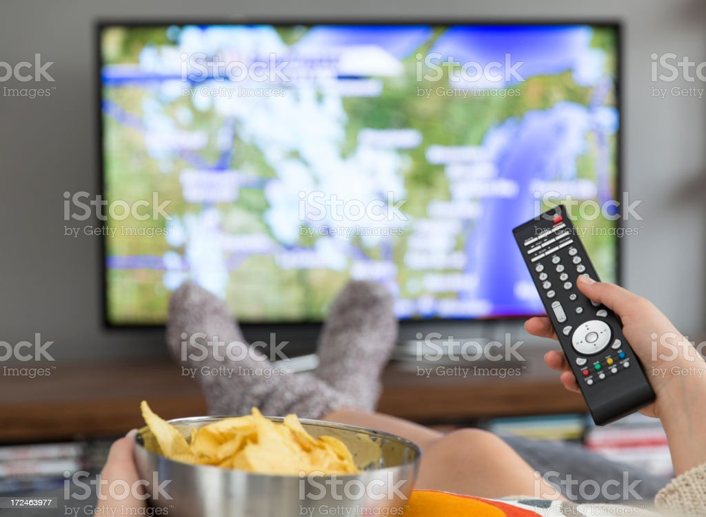 Watching TV with a bowl of crisps stock photo