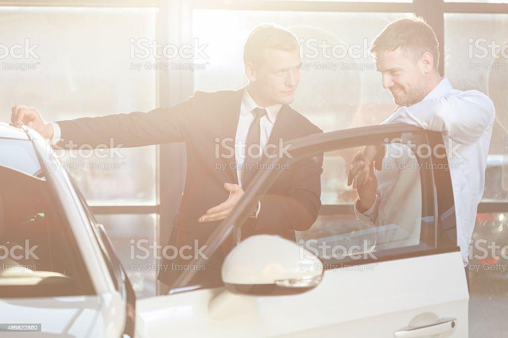 Watching vehicle in dealership stock photo