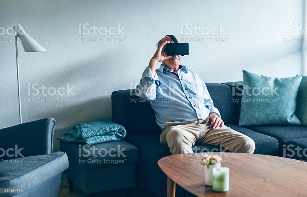 Watching virtual reality content on VR glasses at home stock photo